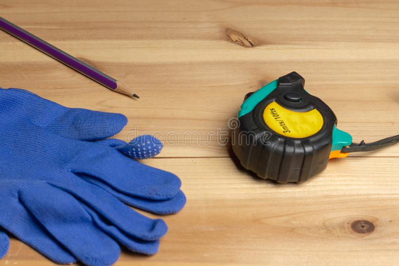 Misura di nastro, guanti blu protettivi e una matita su un pezzo di legno fotografie stock libere da diritti