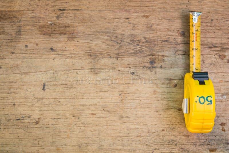 Misura di nastro, misura di nastro sui precedenti di legno marroni fotografie stock libere da diritti