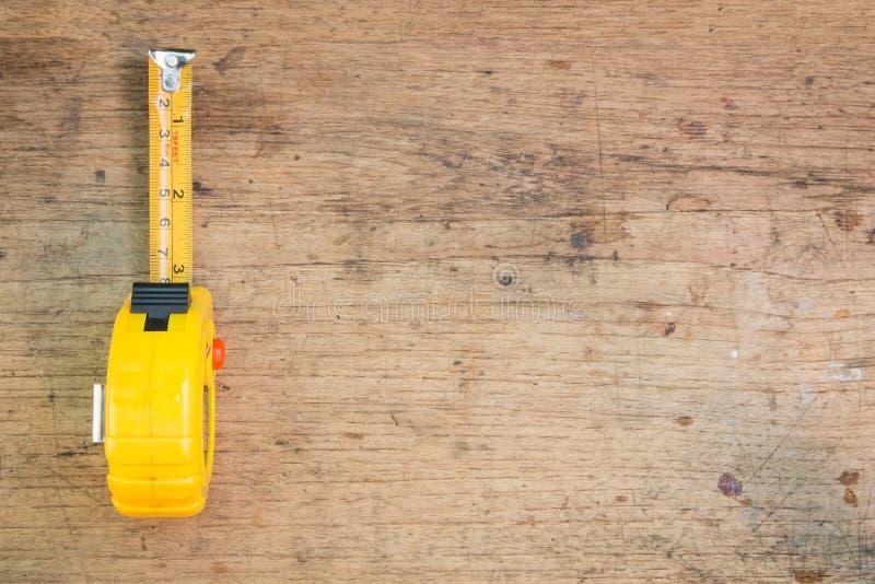 Misura di nastro, misura di nastro sui precedenti di legno marroni immagini stock