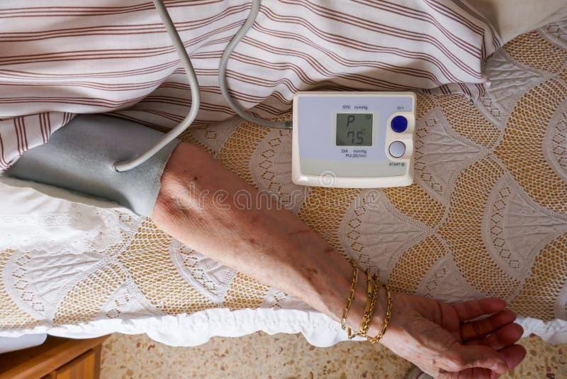 Misura di pressione, una donna che controlla la suoi pressione sanguigna ed impulso sul suo braccio immagini stock