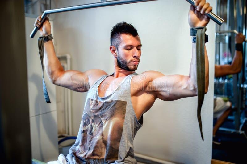 Misura, uomo sexy atletico che risolve nella palestra fotografia stock