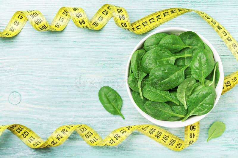 Misura verde delle foglie e di nastro degli spinaci sulla vista di legno del piano d'appoggio Dieta e concetto sano dell'alimento fotografia stock