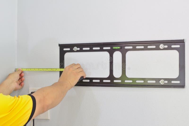 Misurato da una distanza gialla della cartuccia del tester dalla parete Il tecnico installa il dispositivo per appendere la TV su fotografia stock libera da diritti