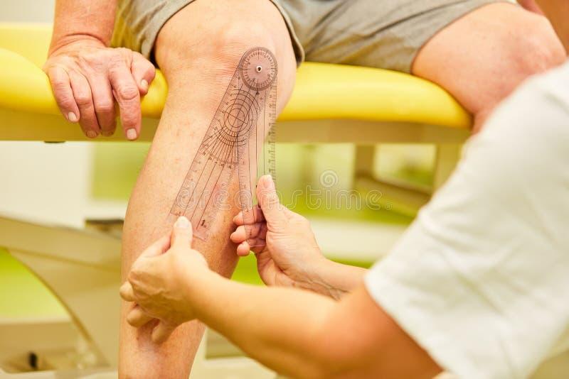 Misurazione della mobilità del giunto di ginocchio con il goniometro immagine stock