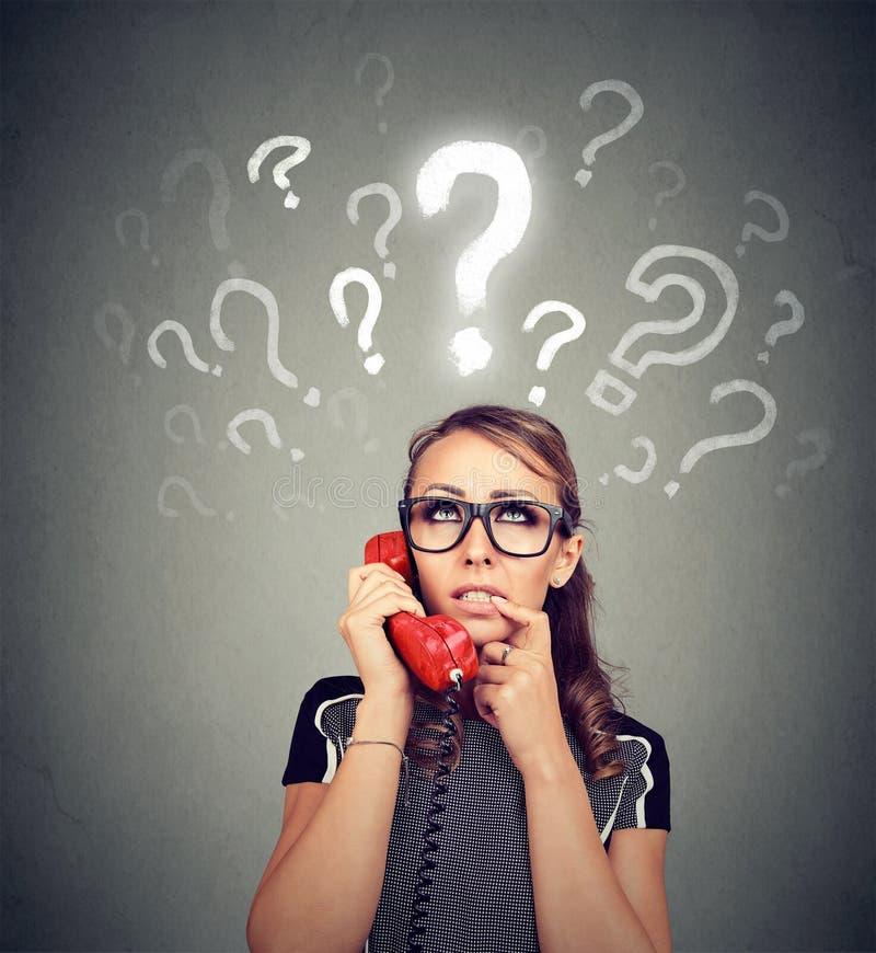 Misverstand en verre vraag Het verstoorde ongerust gemaakte verwarde vrouw spreken op een telefoon heeft vele vragen stock afbeelding