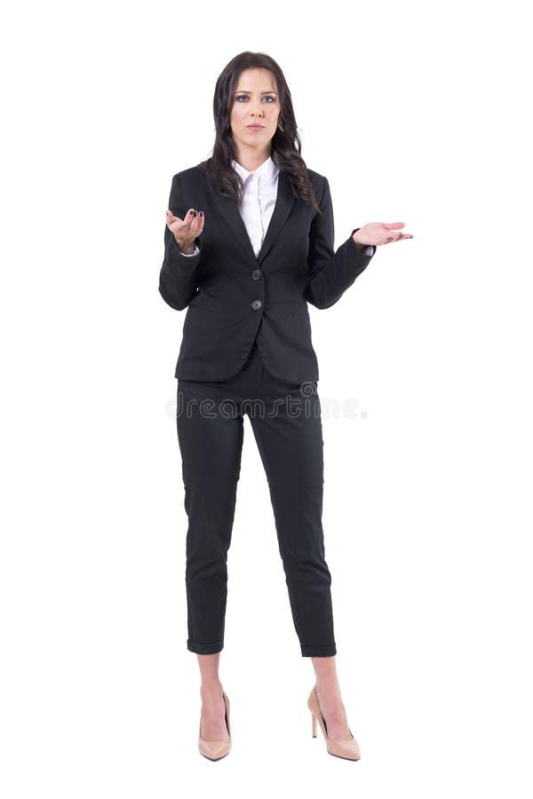 Misverstandconcept Onzekere bedrijfsvrouw die in zwart kostuum schouders ophalen stock afbeelding