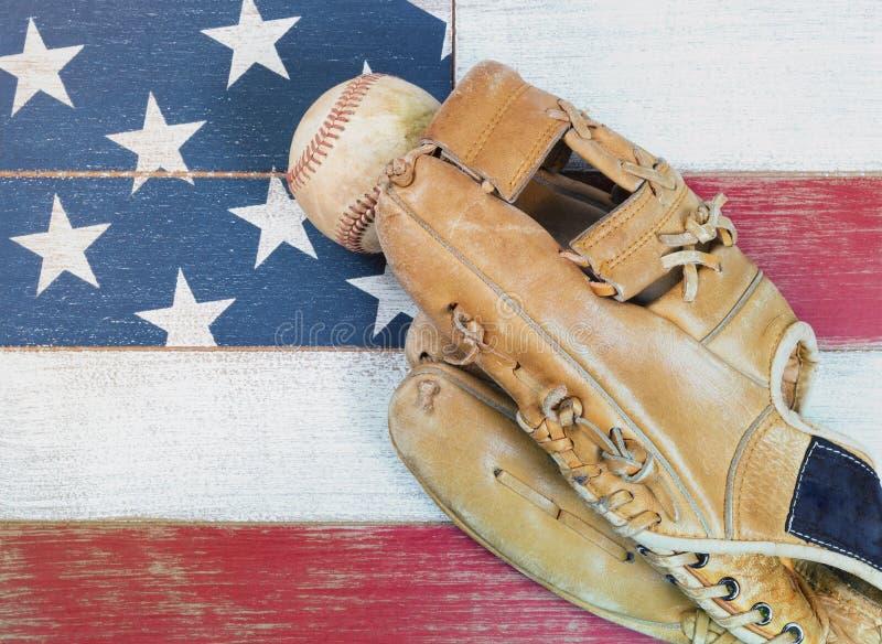 Mitón y bola llevados viejos de béisbol en los tableros descolorados pintados en Ameri foto de archivo libre de regalías