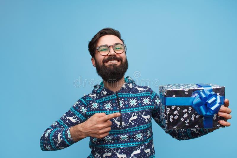 Mit dem Bart, der Finger auf Geschenkbox hält und zeigt lizenzfreies stockbild