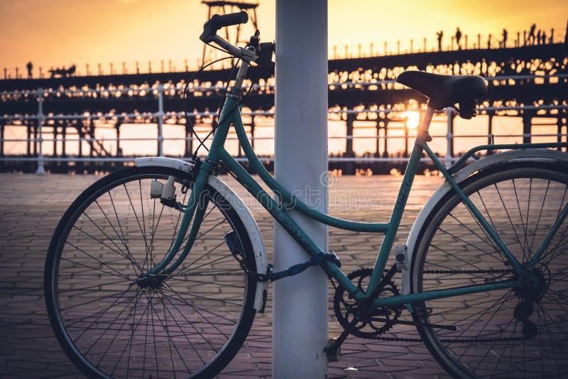 Mit dem Hintergrund eines Sonnenuntergangs auf dem Rio Tinto-Dock, bleibt ein Weinlesefahrrad an einem Pfosten in Huelva, Andalus lizenzfreie stockfotos