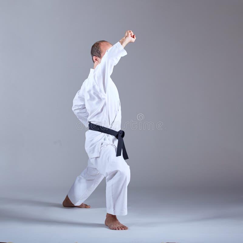 Mit einem schwarzen Gürtel bildet der Athlet den Block mit seiner Hand in einer formalen Karateübung aus lizenzfreie stockfotos