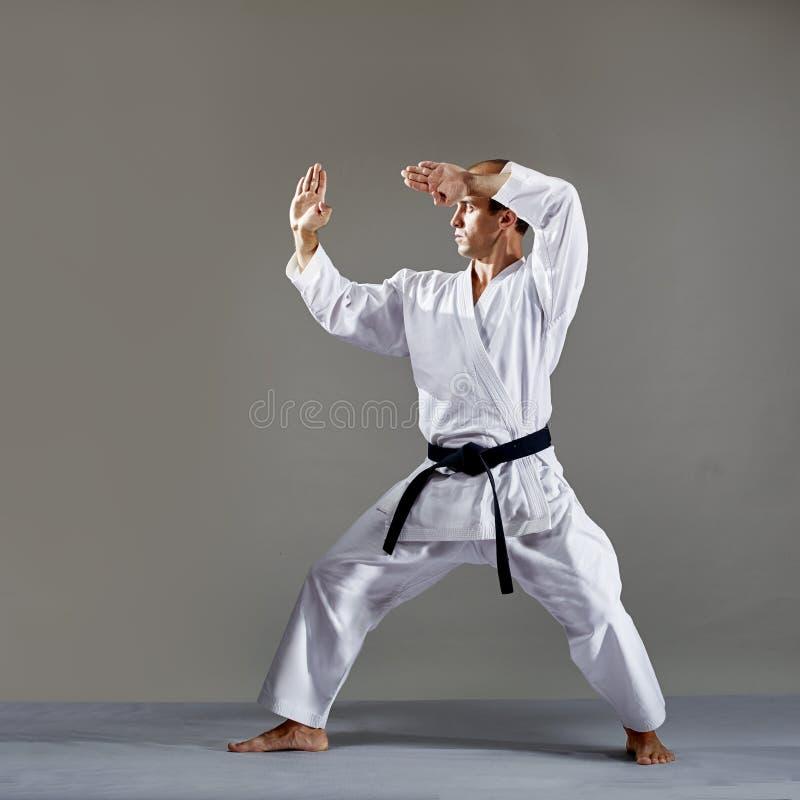 Mit einem schwarzen Gürtel bildet ein Athlet eine formale Karateübung aus lizenzfreie stockbilder