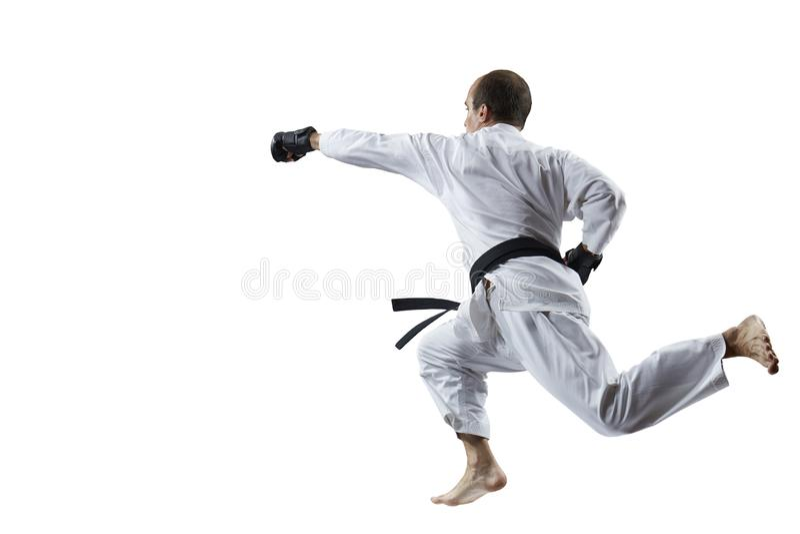 Mit einem schwarzen Gürtel schlägt ein erwachsener Athlet mit einer Hand im Sprung lokalisiert stockfotos