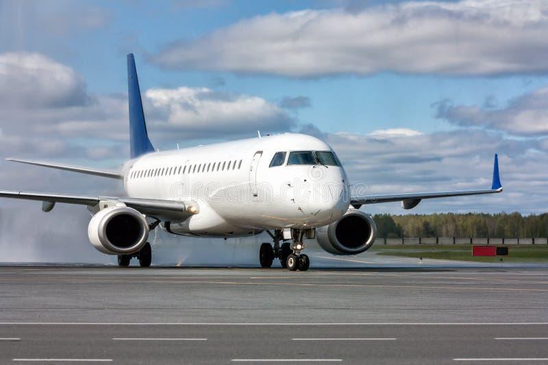 Mit einem Taxi fahren eines weißen Passagierflugzeugflugzeugs nachdem dem Überschreiten durch einen Wasserbogen lizenzfreies stockbild