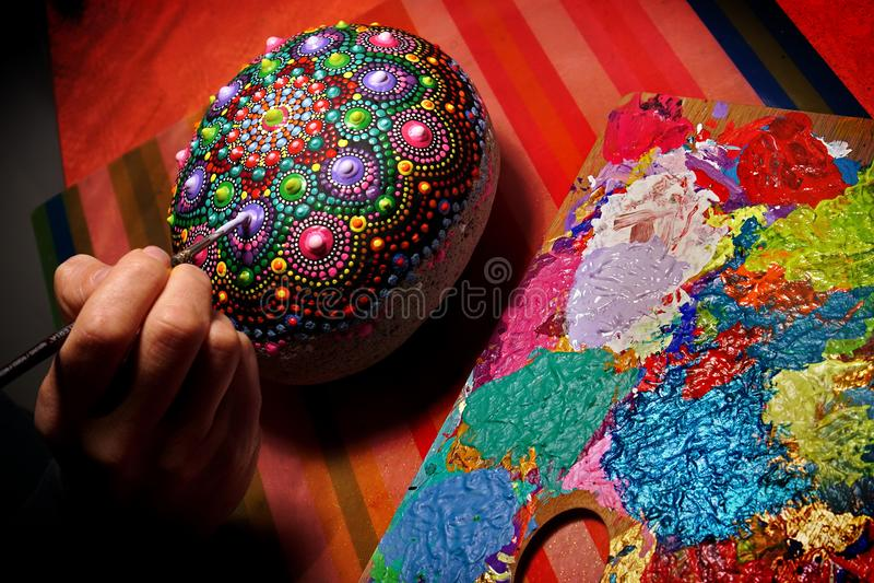 Mit einer Bürste eine Mandala auf einem Stein zeichnen lizenzfreie stockfotografie