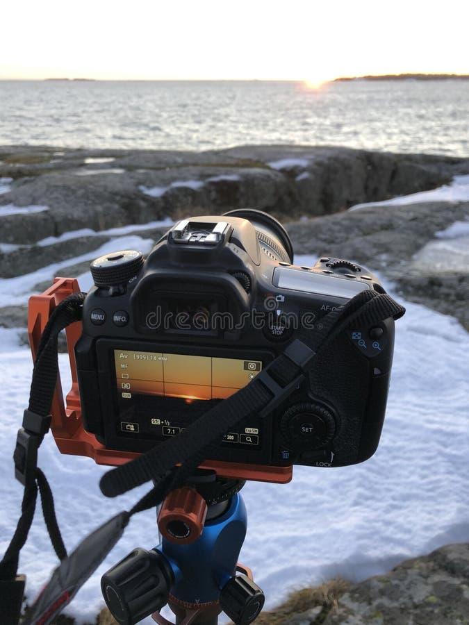 Mit einer Kamera und einem Stativ einen winterlichen Sonnenuntergang aufnehmen lizenzfreies stockbild