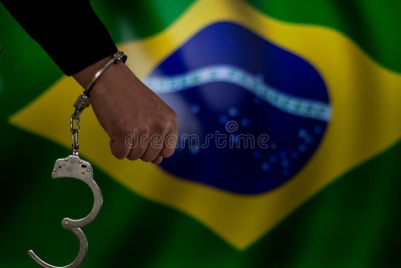 Mit Handschellen gefesselte Hand vor der Landesflagge Übergeben Sie das Anhalten einer Pistole vor Backsteinmauer mit rauem Schat lizenzfreies stockbild