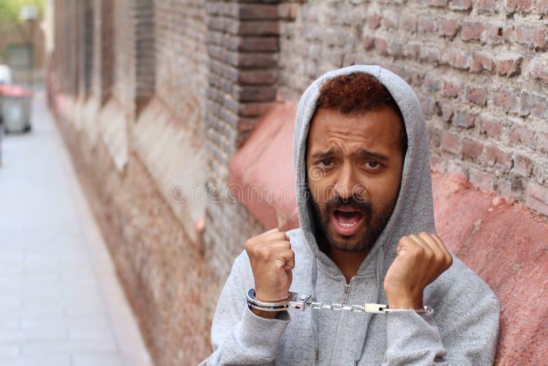 Mit Handschellen gefesselter ethnischer Mann nah oben festgenommen stockfotografie
