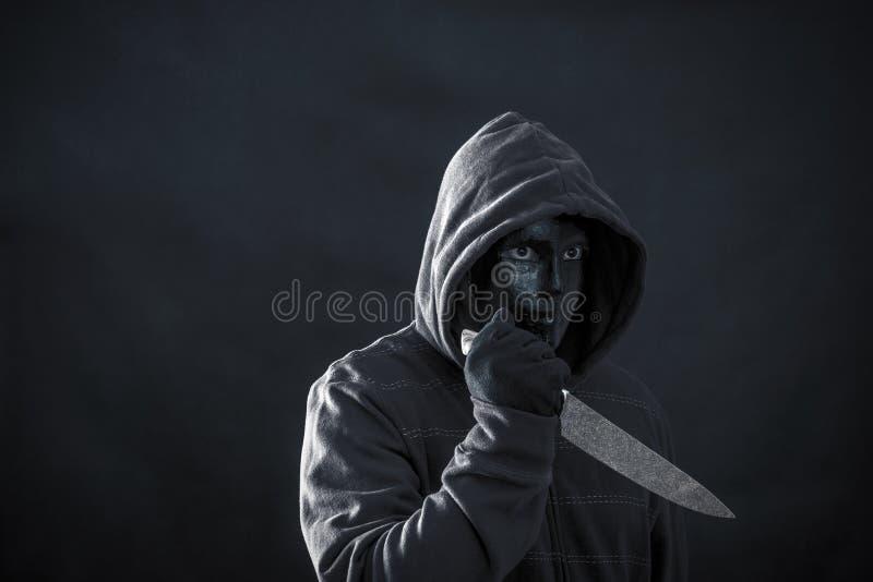 Mit Kapuze Mann mit schwarzem Maskenholdingmesser stockfotos