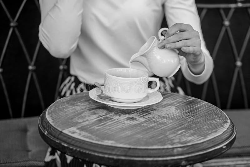 Mit Milch schmeckt besser Tipps für das gesündere Kaffeetrinken Übergeben Sie die Frau, die draußen auslaufende Milch schwarzem K stockfotos