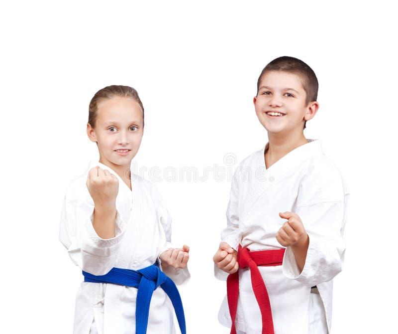 Mit rotem und blauem Gurt stehen die Kinder im Gestell von Karate lizenzfreie stockfotos