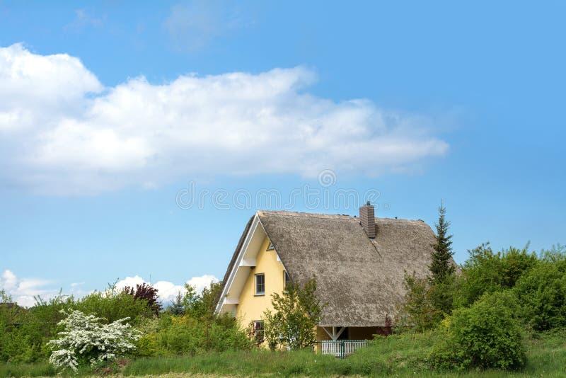 Mit Stroh gedecktes Häuschen in der grünen Landschaft gegen einen blauen Himmel, ty lizenzfreie stockbilder