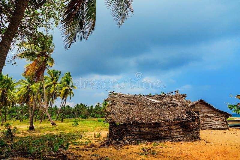 Mit Stroh gedecktes Kokosnussblatthaus oder Fischenhütte auf tropischem Strand lizenzfreie stockfotografie
