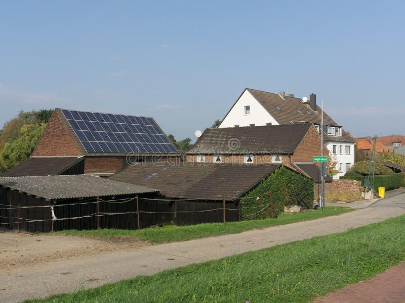Mit Ziegeln gedeckte Dächer von ländlichen Steinhäusern mit einer Solarbatterie in den europäischen Vororten stockbild