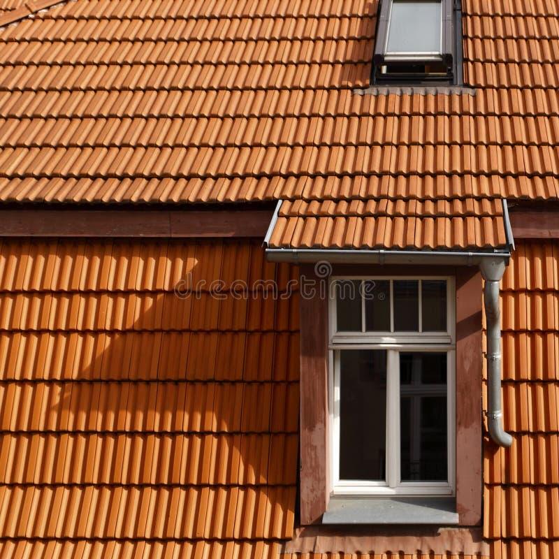 Mit Ziegeln gedecktes Dach und Fenster stockbilder