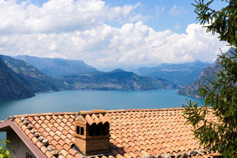 Mit Ziegeln gedecktes Dach und Panorama von See Iseo gegen den Hintergrund von Bergen und von umfangreichen Wolken, Italien stockfotografie