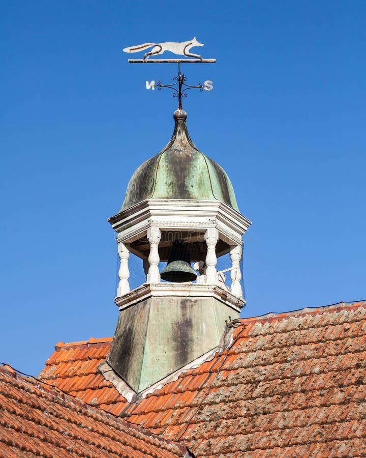 Mit Ziegeln gedecktes orange Dach mit Glockenturm und Fox-Wetterfahne stockfotos