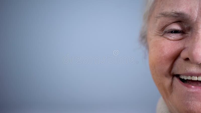 Mitad-cara del fondo gris sonriente de la mujer mayor, Seguridad Social, humor positivo imagenes de archivo