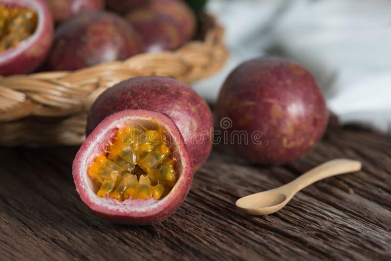 Mitad de la fruta de la pasión y del passionfruit orgánico en la cesta de madera, fondo de madera imágenes de archivo libres de regalías