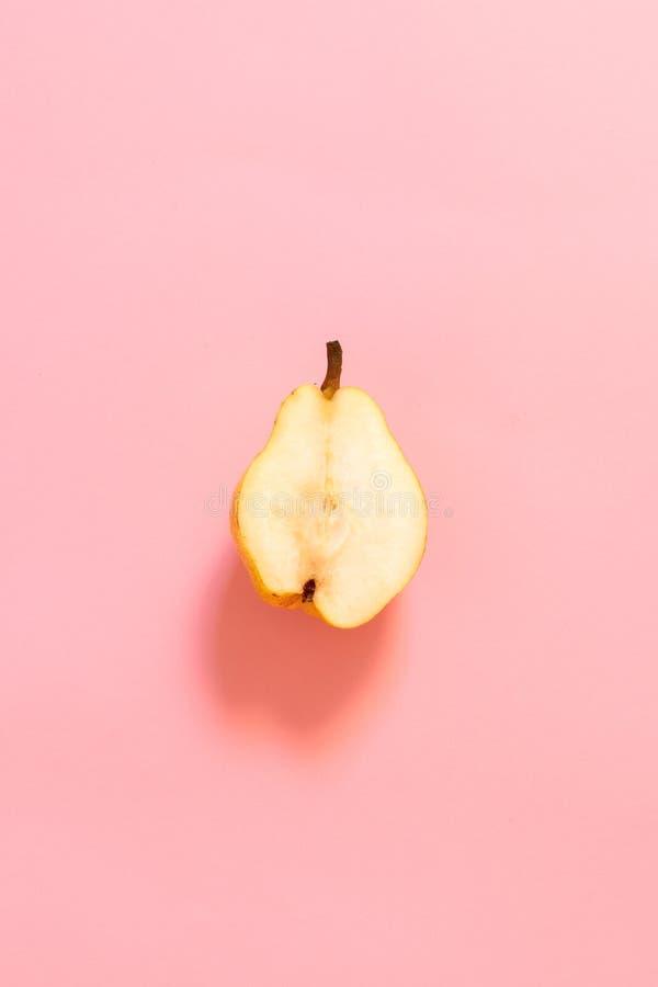 Mitad de la pera del amarillo del corte en un fondo del rosa en colores pastel foto de archivo libre de regalías