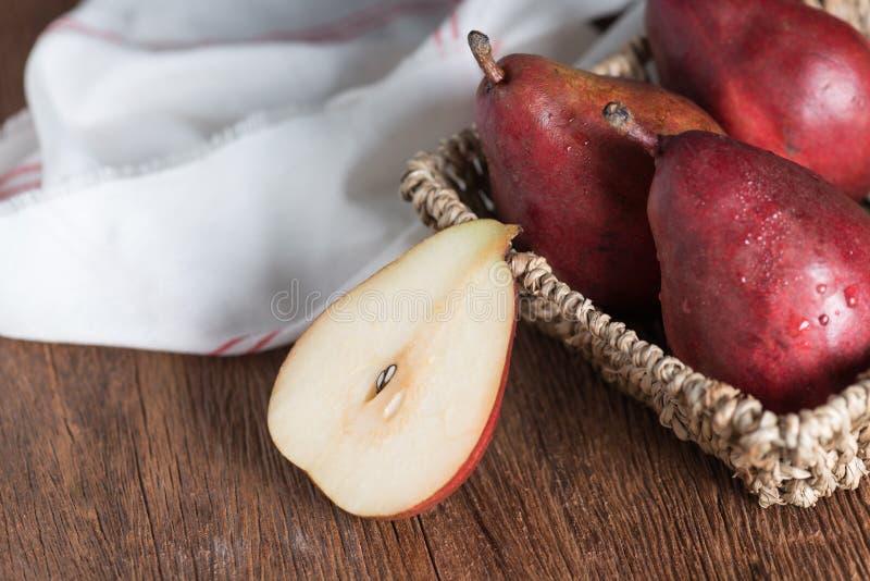 Mitad de la pera roja y de la pera roja en cesta foto de archivo libre de regalías
