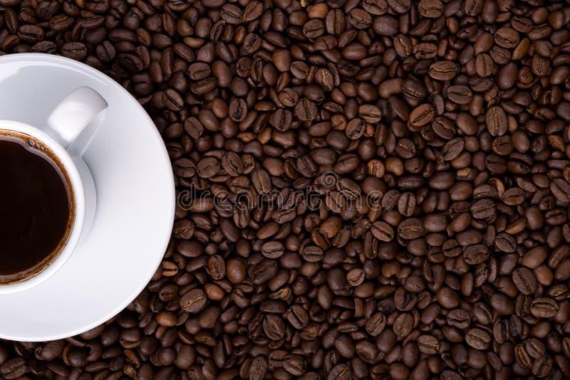 Mitad de la taza de café en el fondo hecho de los granos de café foto de archivo libre de regalías