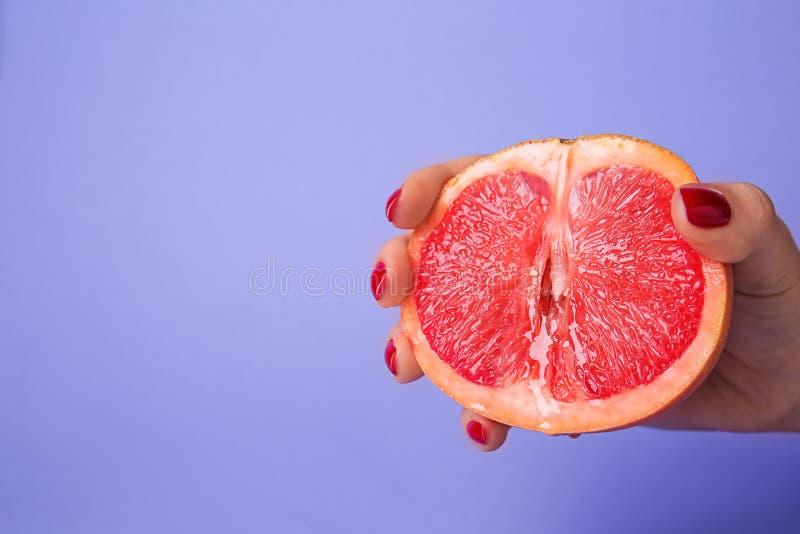 Mitad de la tenencia de la mujer del pomelo jugoso en fondo del color Concepto er?tico fotografía de archivo
