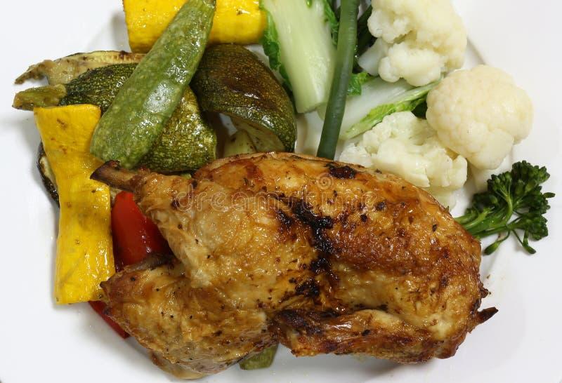 Mitad de un pollo asado a la parrilla y verduras imagen de archivo