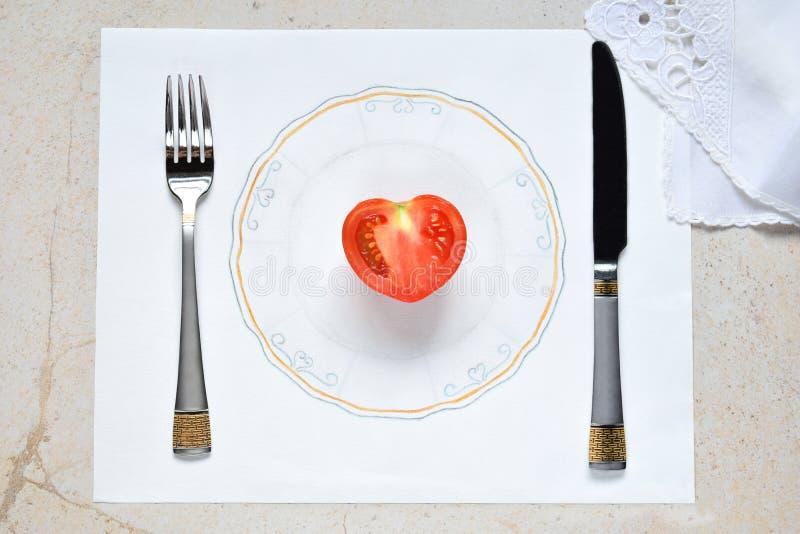 Mitad de un tomate bajo la forma de corazón en una placa pintada Concepto de comida vegetariana Restricciones en la comida Pequeñ imagenes de archivo
