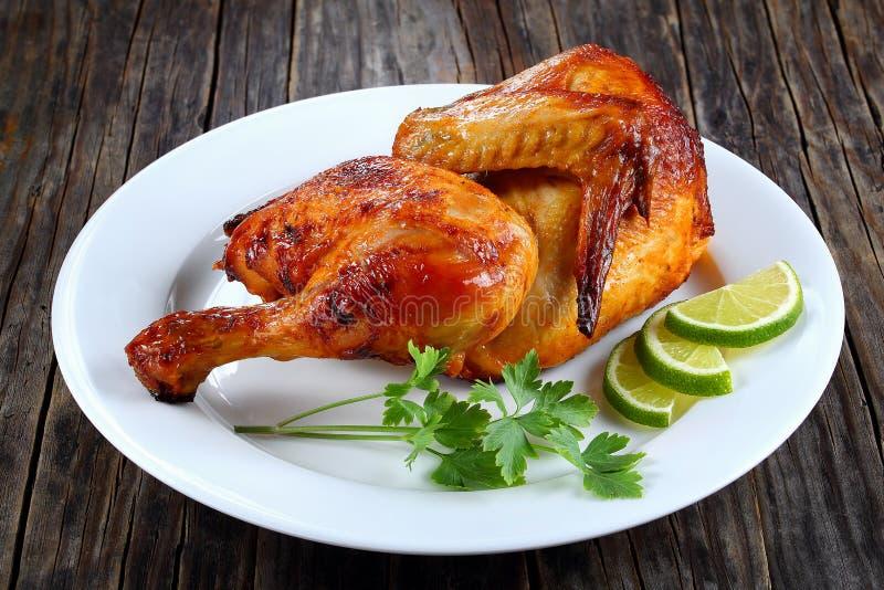 Mitad del pollo asado a la parrilla apetitoso en la placa imágenes de archivo libres de regalías