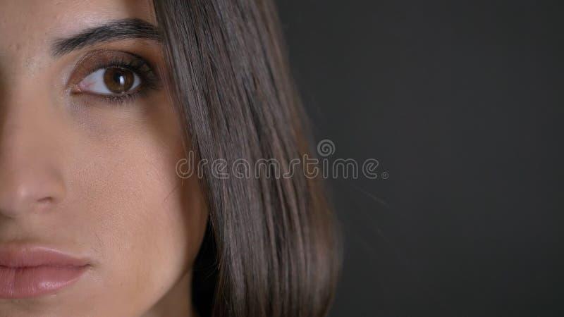 Mitad-retrato del primer de la muchacha de pelo largo bonita joven en camisa plaided que mira seriamente hacia la izquierda en ne fotografía de archivo