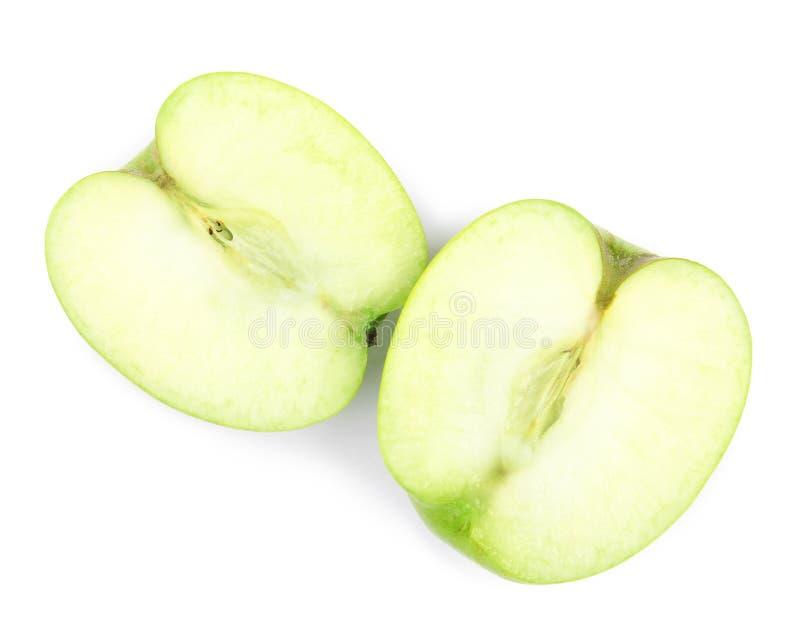 Mitades de la manzana verde fresca en el fondo blanco imagen de archivo