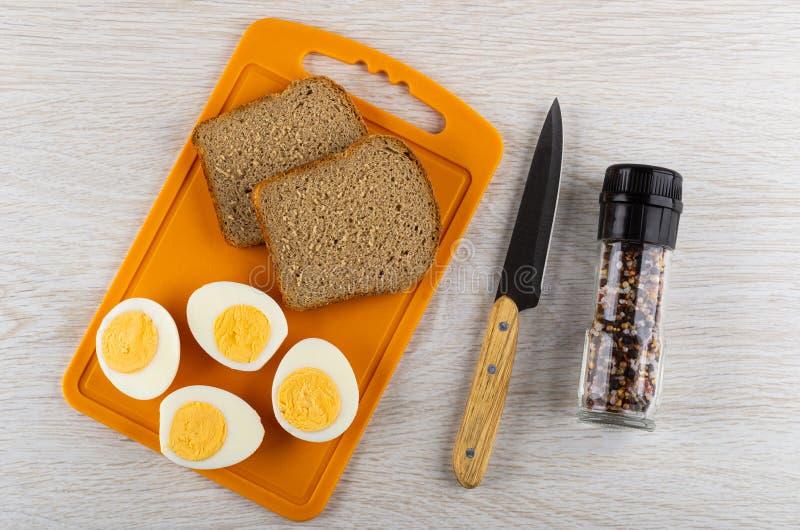 Mitades de los huevos hervidos, pan en la tabla de cortar, cuchillo, tarro con el condimento en la tabla de madera Visi?n superio fotos de archivo libres de regalías