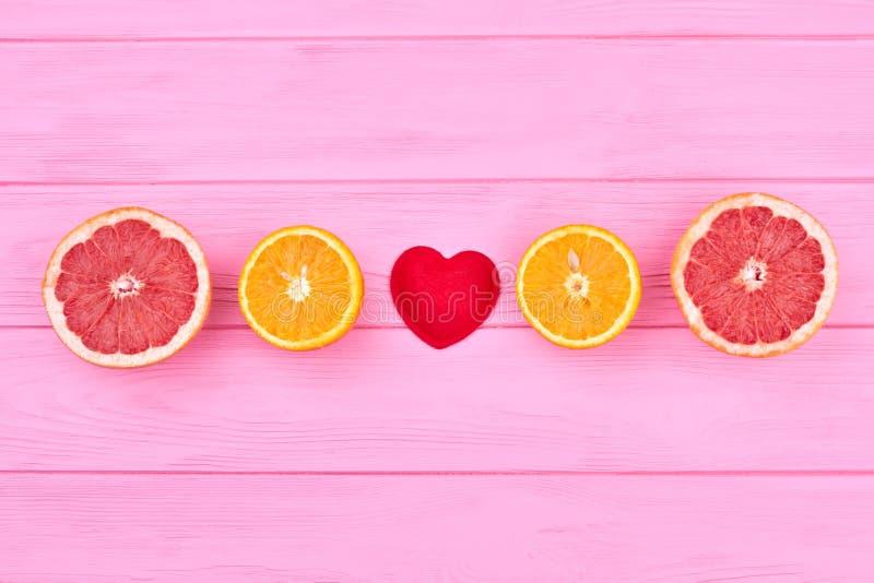 Mitades del pomelo y de la naranja en la madera rosada fotografía de archivo libre de regalías