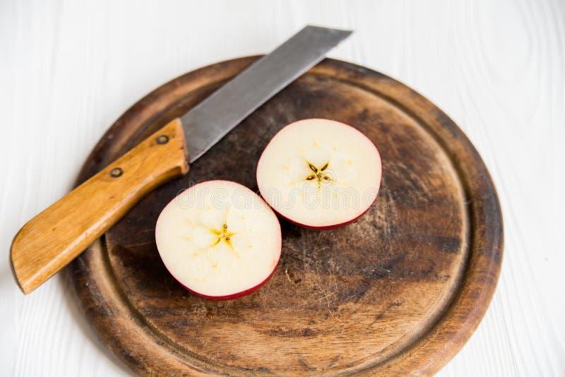 Mitades rojas de la manzana con el cuchillo en cierre de la tabla de cortar foto de archivo