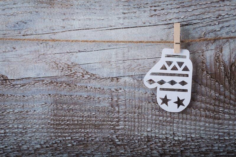Mitaine de papier de Noël accrochant au-dessus du fond en bois photos stock