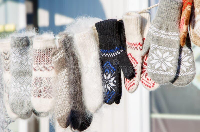 Mitaines au marché de Noël d'hiver Un coloré de variété tricoté des mitaines de laine accrochant sur une corde Cadeau de Noël ou image stock