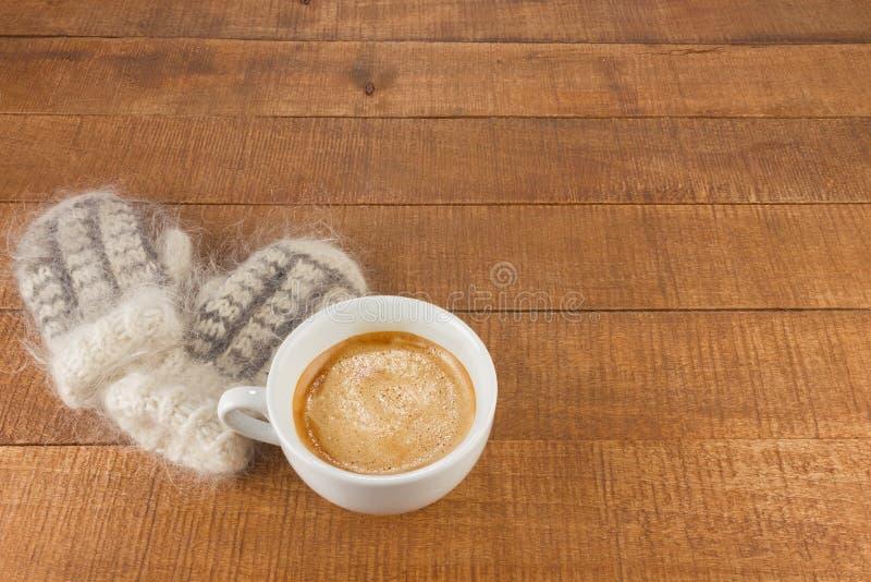 Mitaines de laine avec la tasse de café aromatique frais photo stock
