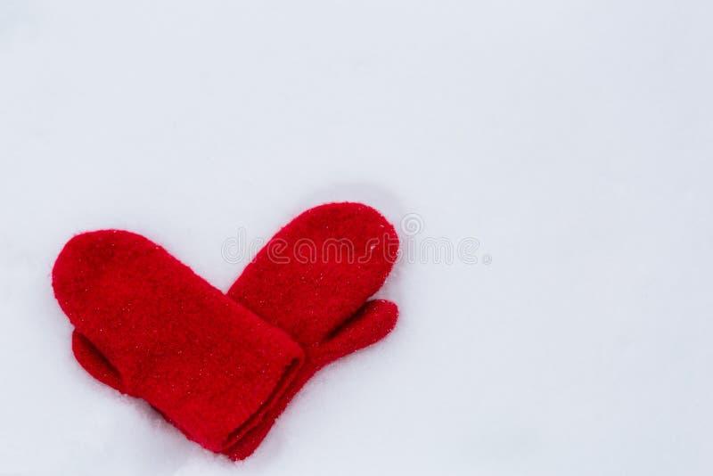 Mitaines en forme de coeur sur la neige images libres de droits
