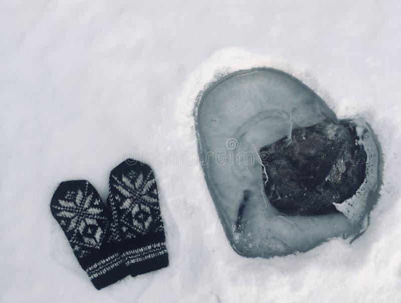 Mitaines sur la neige près de la glace en forme de coeur images libres de droits