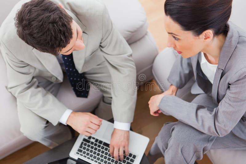 Mitarbeiter, die den Laptop sitzt auf Sofa sprechen und verwenden lizenzfreie stockfotos